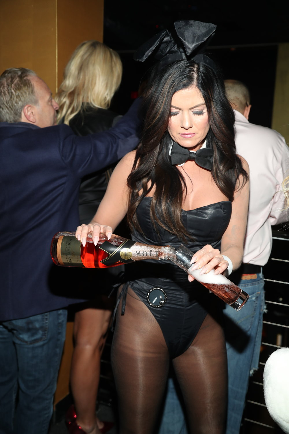 Playmate serving a bottle of Möet