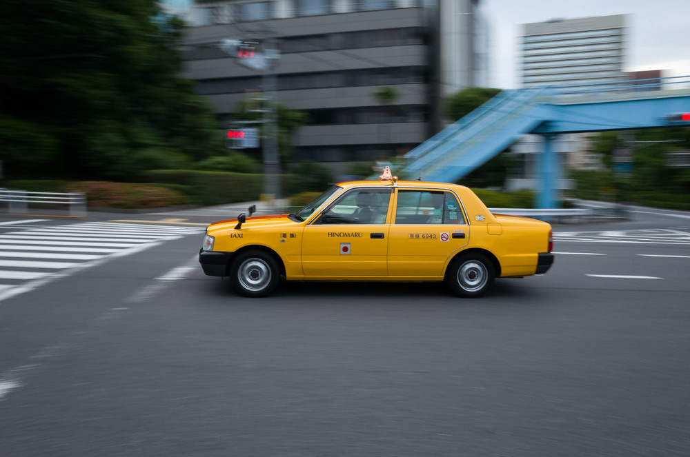 A Hinomaru taxi whizzing its way through empty streets