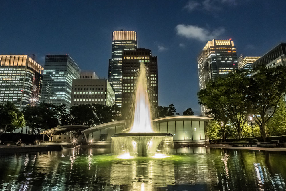 The fountains are on as well as the lights of the Marunouchi skyscrapers behind