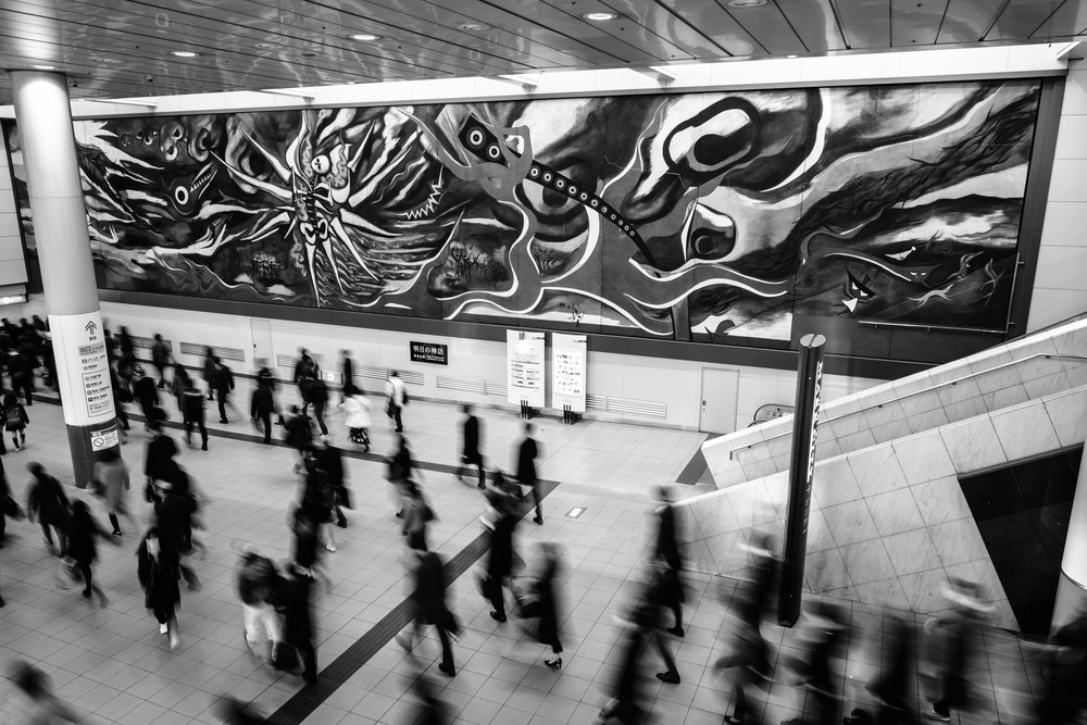 "Commuters passing, ""The Myth of Tomorrow"", at Shibuya station"