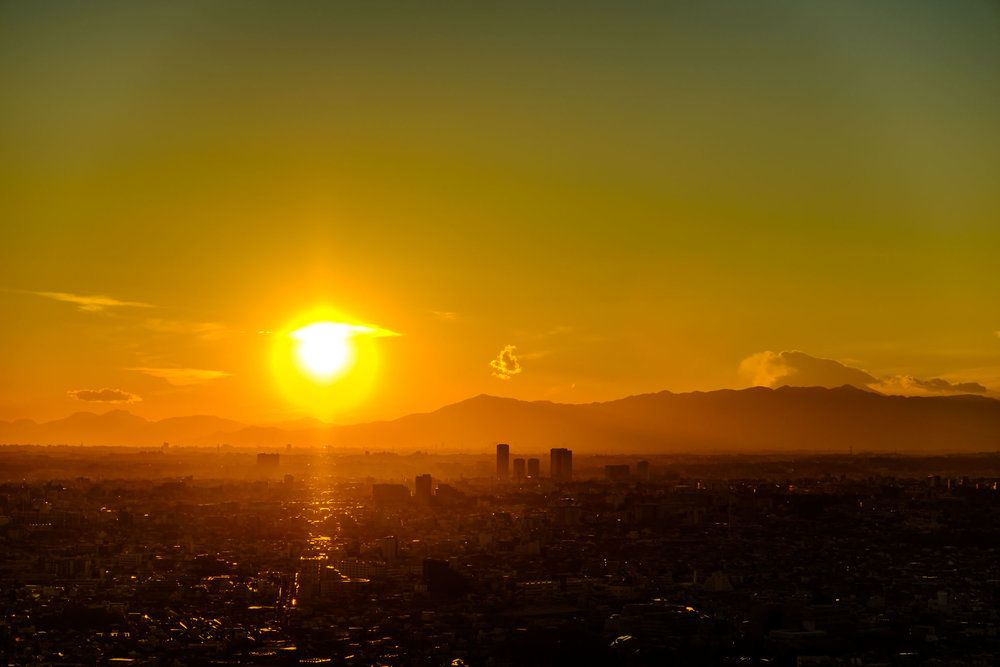 Looking west at sunset, nothing but suburban Tokyo and Mt. Fuji behind the clouds to the right.