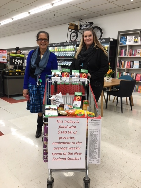 Miraka and Jo showing a trolley filled with $140 worth of groceries, equivalent to the average weekly spend of NZ smoker.