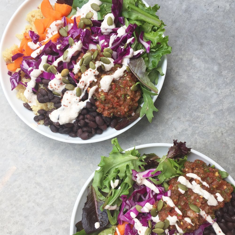Mexican-inspired bowls with quinoa, black beans, chopped carrot, raw red cabbage, baby mixed lettuce, homemade salsa, cashew-lime cream, pumpkin seeds, chunky red salt.
