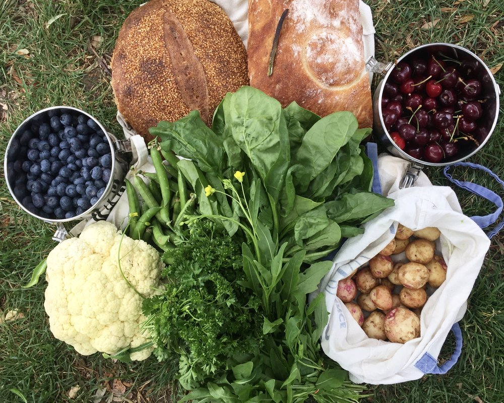 A Trout Lake farmers market haul: blueberries, two loaves of sourdough, cherries, new potatoes, spinach, arugula, parsley, cauliflower, English peas