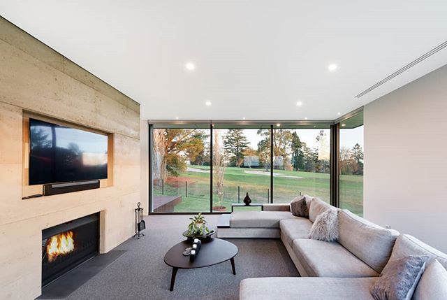 Lounge with a rammed earth fireplace and golf course views. Yes please! 😍 Interiors by us, architecture by @design_unity, built by #herbelconstructions 📷 by #matthewmallett  #warragulresidence #martinjscottdesign  #mjs #residentialdesign