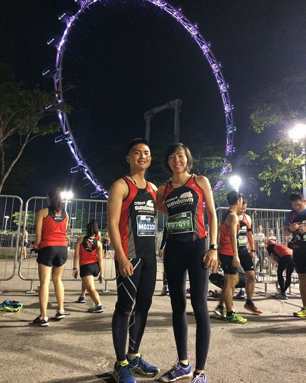 A photo together before walking to the start point. In the background shows the Singapore Flyer.