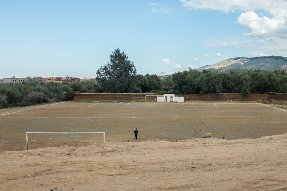 A lonely player on the football field in the valley.