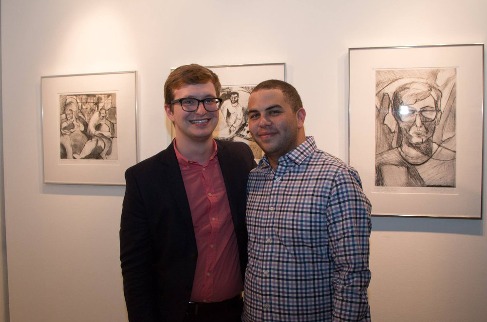 Two Ohioans, Micah Zavacky and his partner Anthony Birchfield in front of Micah's drypoints. Photo courtesy: Justine Kaszynski Photography.