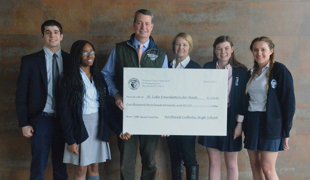 A group of students present a check to St. Luke