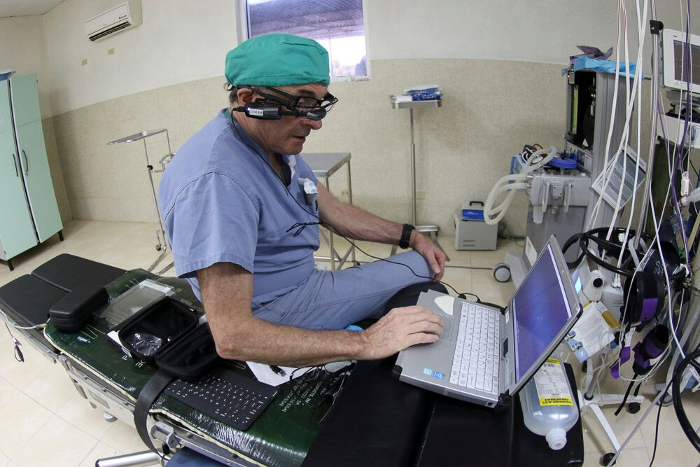 A medical volunteer consults his laptop