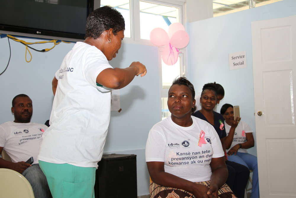 Yolette Senat (center) participates in an educational skit at a breast cancer screening event at St. Luke Hospital.