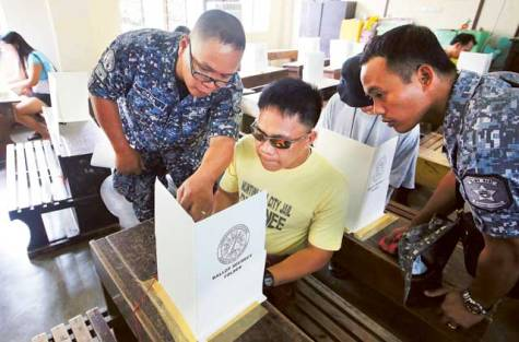 Detainee casts election ballot at a local school used as a polling station in Taguig city, south of Manila, Philippines.