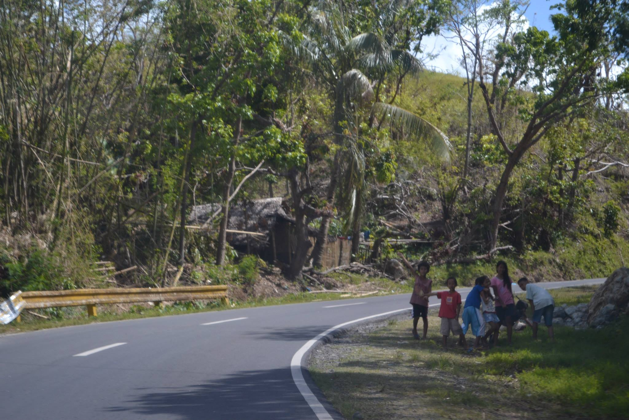 A common sight along the highways: children reaching their hands out for help.