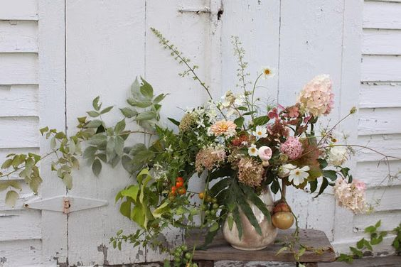 A wild and unruly arrangement fresh from the garden featuring cosmos, limelight hydrangea, raspberry foliage, zinnias. coral bells and yes, those are cherry tomatoes.