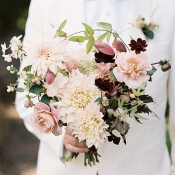 A blushing bouquet full of garden roses, chocolate cosmos, clematis vine and large fluffy dahlias. While being wild and true to the season, this bouquet still retains an elegant and classical shape.