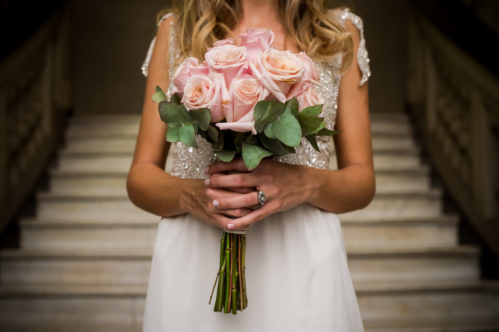 Detail of the bouquet, with roses and eucalyptus leaves, as well as the engagement ring.