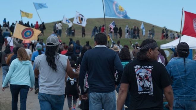 C.NORTHCOTT On most days, demonstrations take place along the road leading to the Dakota Access pipeline construction site. Participants wave flags representing different tribal nations. In some cases, they obstruct trucks and diggers approaching the pipeline. Over 20 Native American protesters have been arrested in the month of August, including the chairman of the Standing Rock Sioux Tribe, David Archambault II.