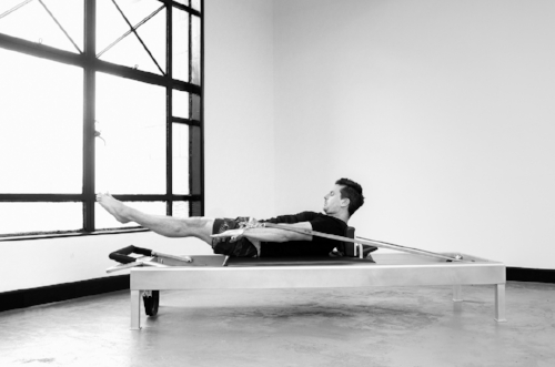 Trevor demonstrating The Hundred on the Universal Reformer at Proper Pilates Melbourne