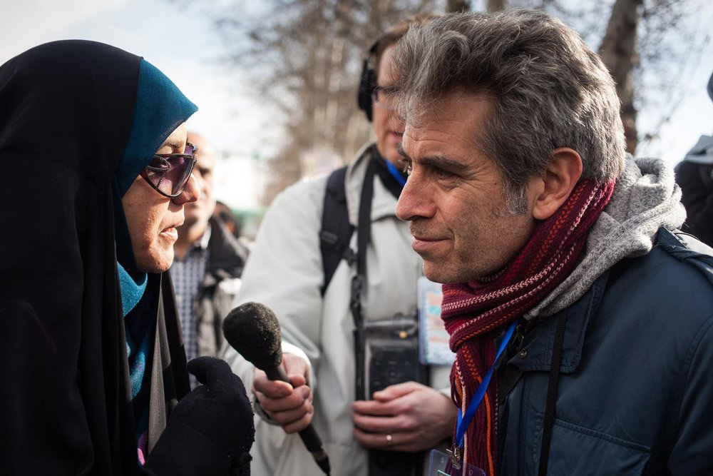 Host Marco Werman speaks with a school teacher at a rally in Tehran. (Credit:  Mahya Rastegar)
