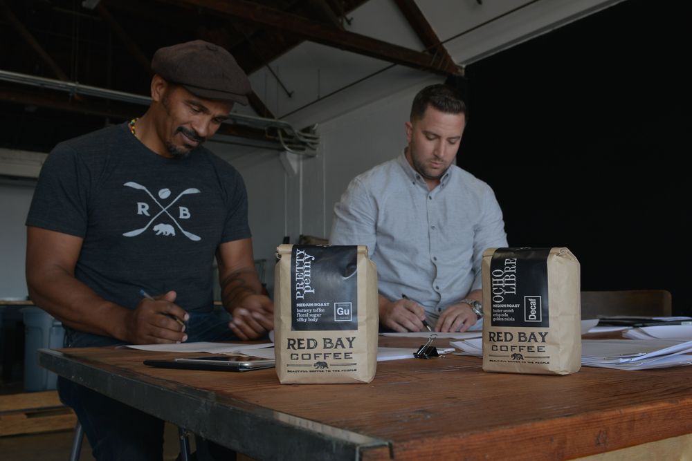 Keba Konte and Sean Murphy executing investment documents at Red Bay Coffee's East Oakland, CA warehouse.