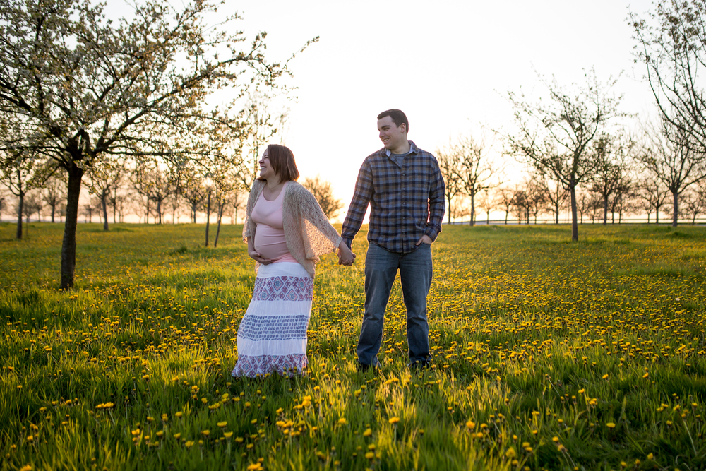 Husband and pregnant wife laugh in field