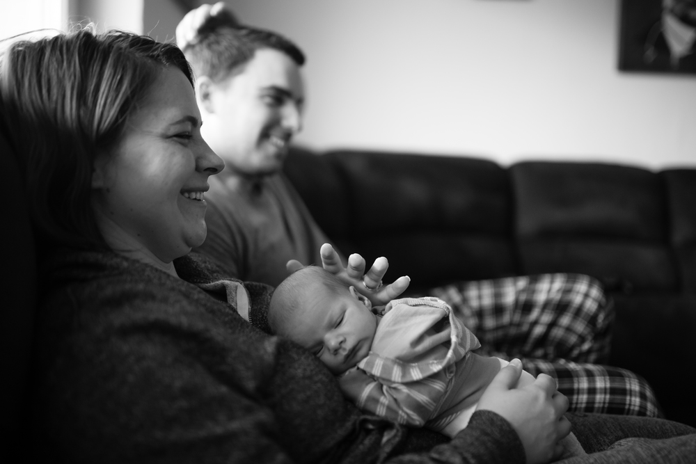 Husband and wife laugh while wife holds baby
