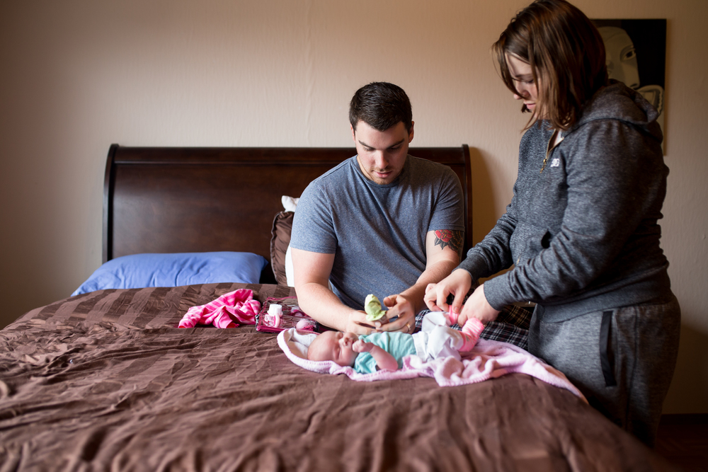 Mom and dad dress baby on bed