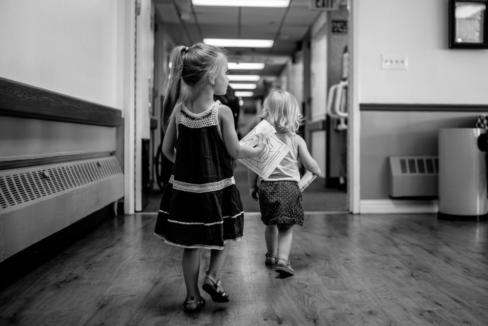 Girls walking down hallway of nursing home