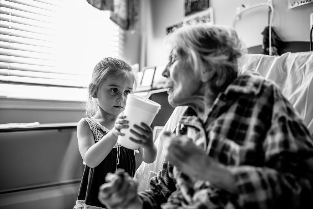 Girl helps great-great-grandmother drink from straw