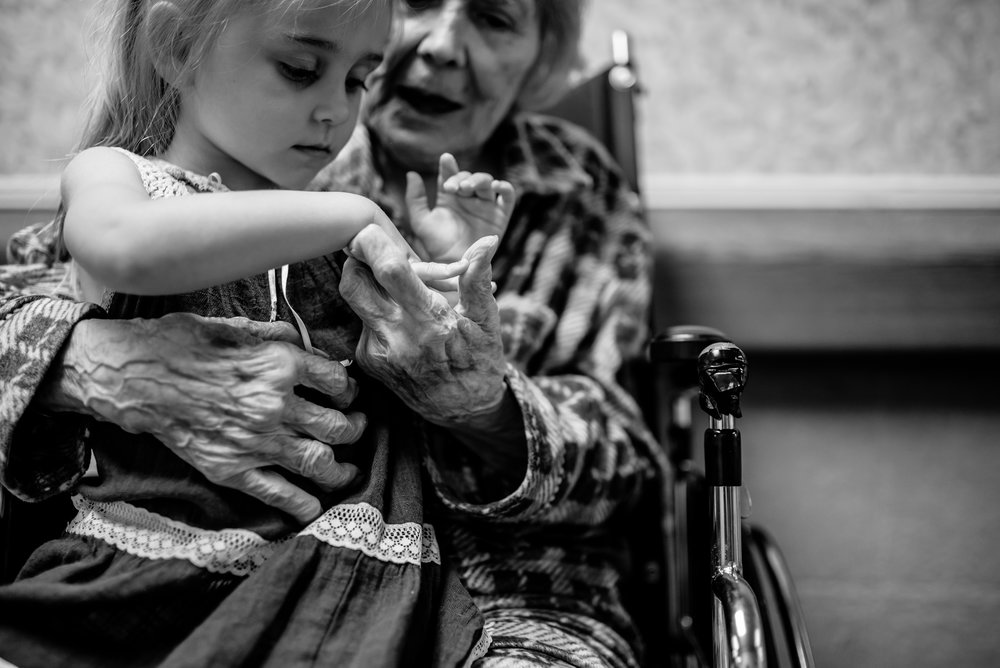 girl touches great-great-grandmother's hand