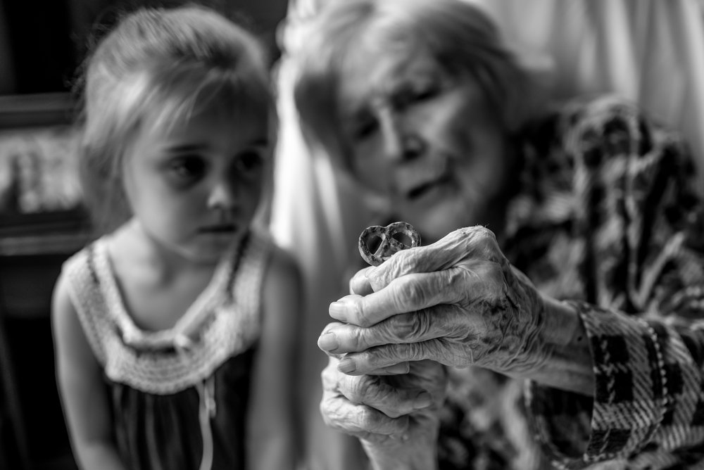 Girl and great-great-grandmother look at Glutino pretzel together