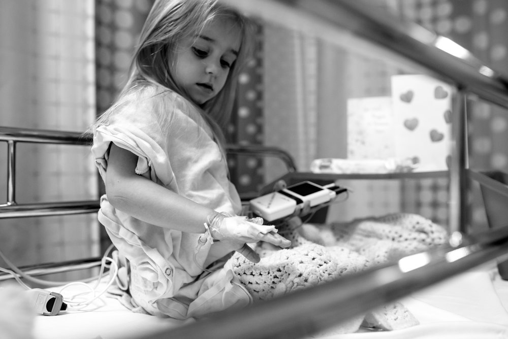 Girl looks at IV port and EKG monitor after congenital heart defect repair procedure