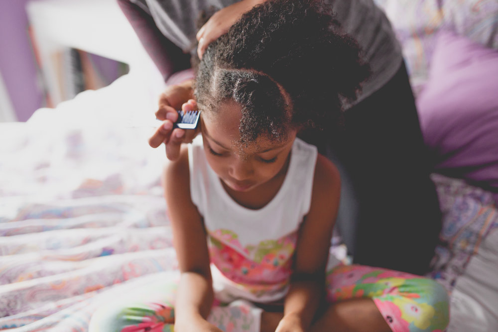 Girl looks down as mom parts her hair for cornrows