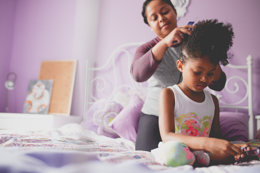 Mom and daughter on bed while mom puts cornrows in daughter's hair