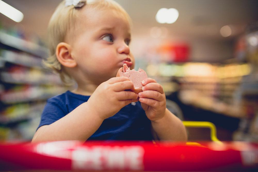 Toddler girl eats fleischwurst (bologna) in grocery cart