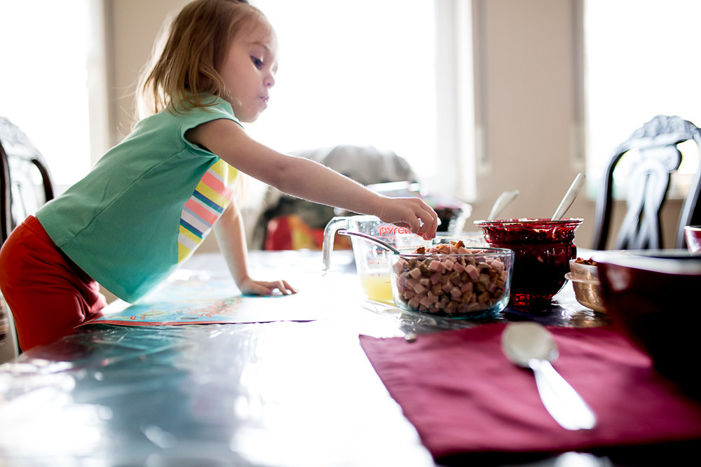 Child reaches across table for a sample from a bowl of meat