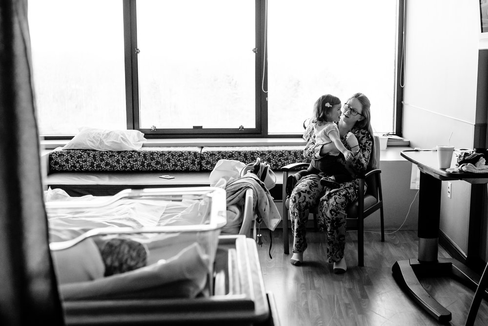 Mom holds daughter in hospital room chair