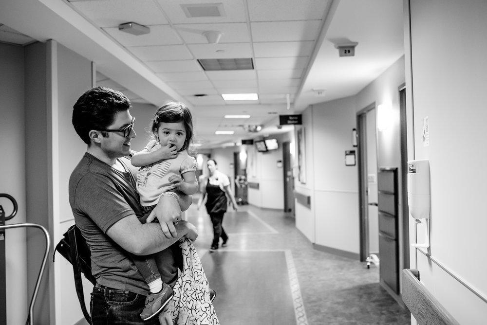 Dad holds daughter in hospital hallway