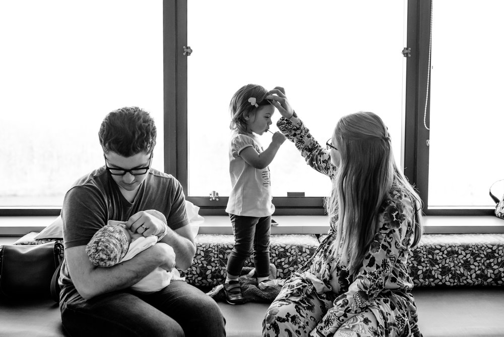 Mom fixes daughter's hair while Dad holds newborn son.
