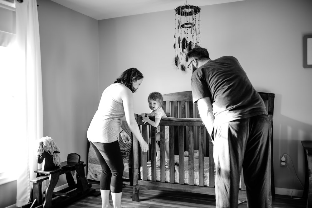 Mom and Dad greet baby in crib