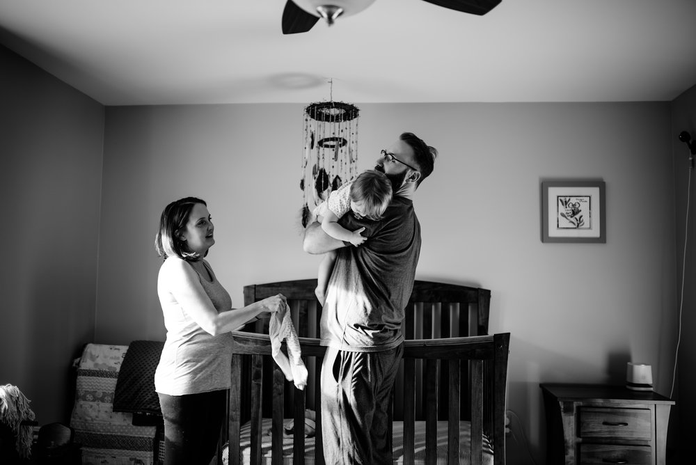 Mom watches as Dad hugs daughter in her nursery