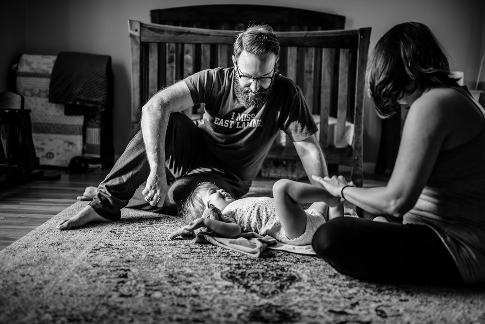 Mom and Dad change daughter's diaper on rug