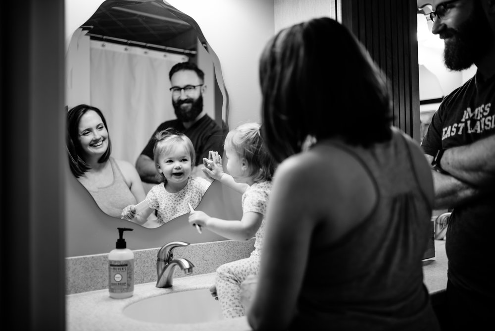 Parents and daughter smile at their reflection in bathroom mirror