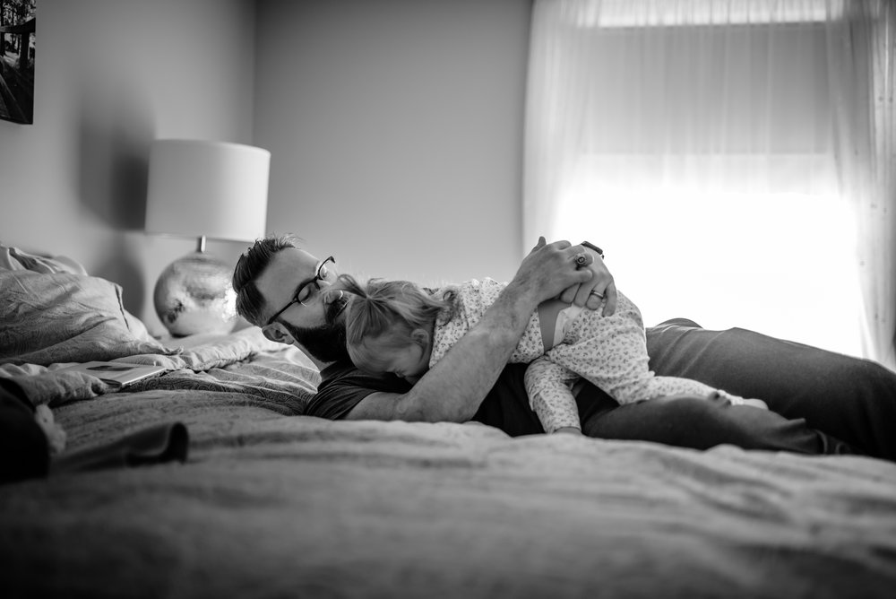Dad hugs daughter atop bed