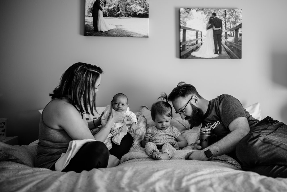 Family gathered on bed; Mom burps infant, Dad and older child look at phone