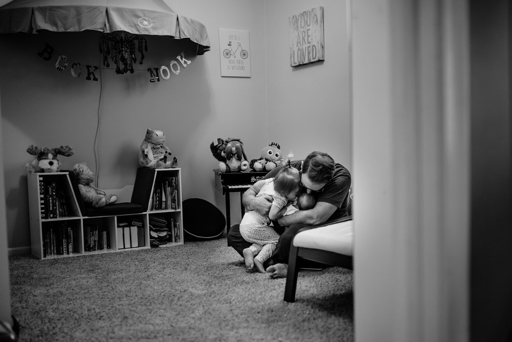 Dad hugs his two daughters in playroom