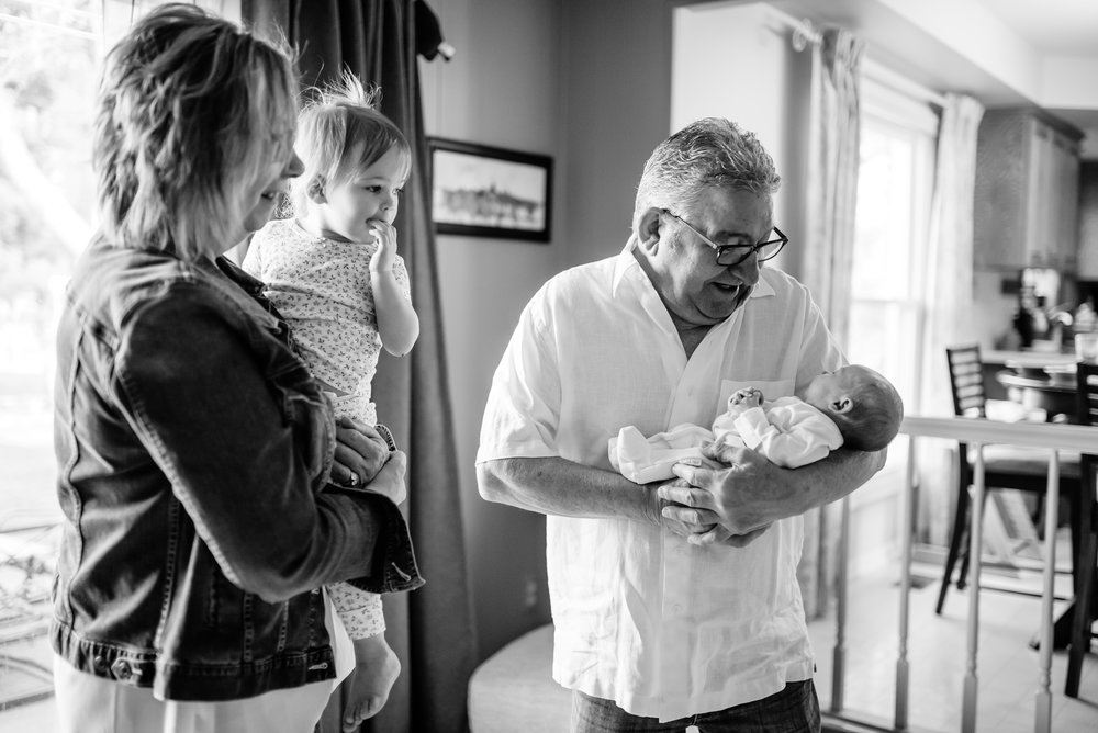 Grandma holds toddler, Grandpa holds newborn, all look at newborn