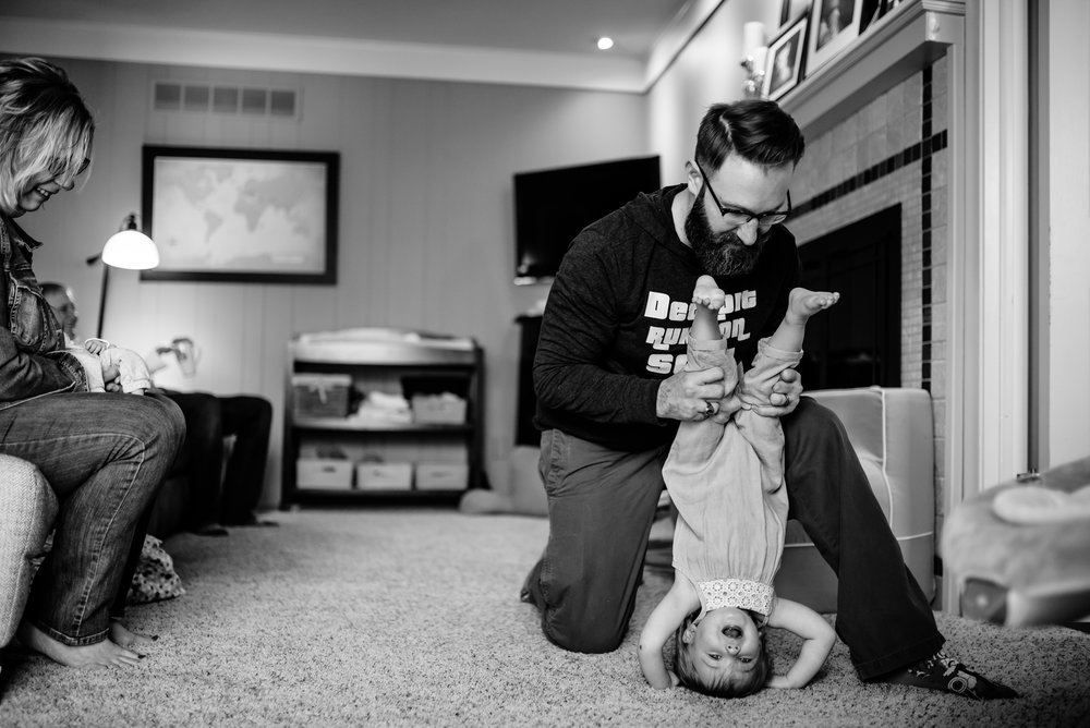 Dad plays with daughter and holds her upside-down