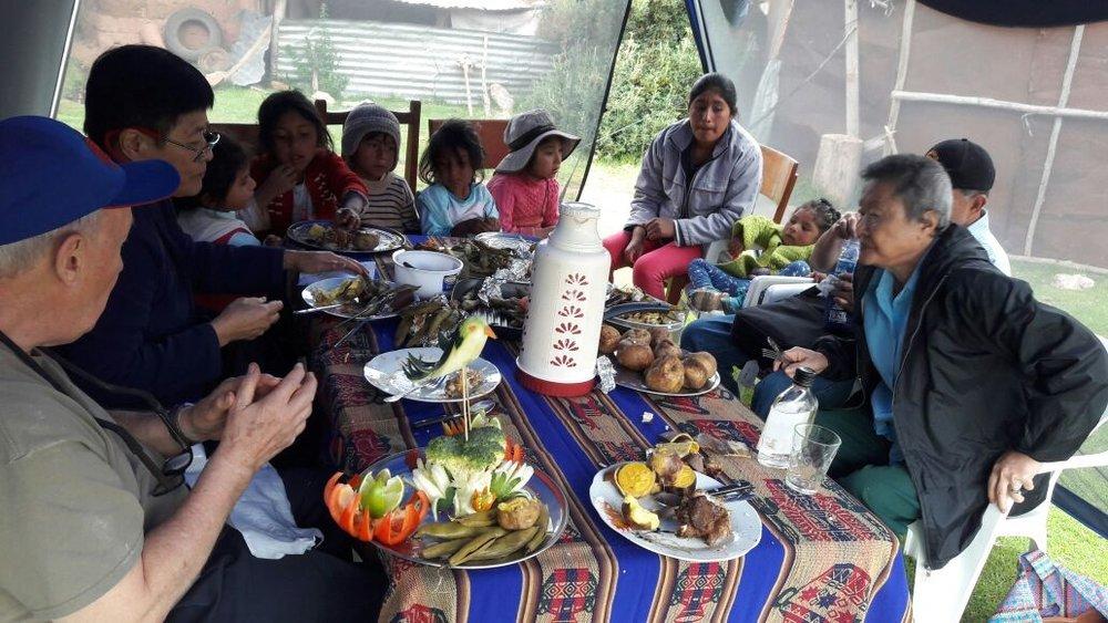 Pachamaca Lunch - Sharing pachamanca lunch with children at the Pillaray school with customers of Valentin's Pachamama Journeys
