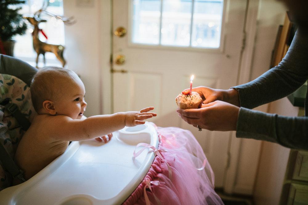 baby-girl-reaching-for-first-birthday-cupcake-roanoke